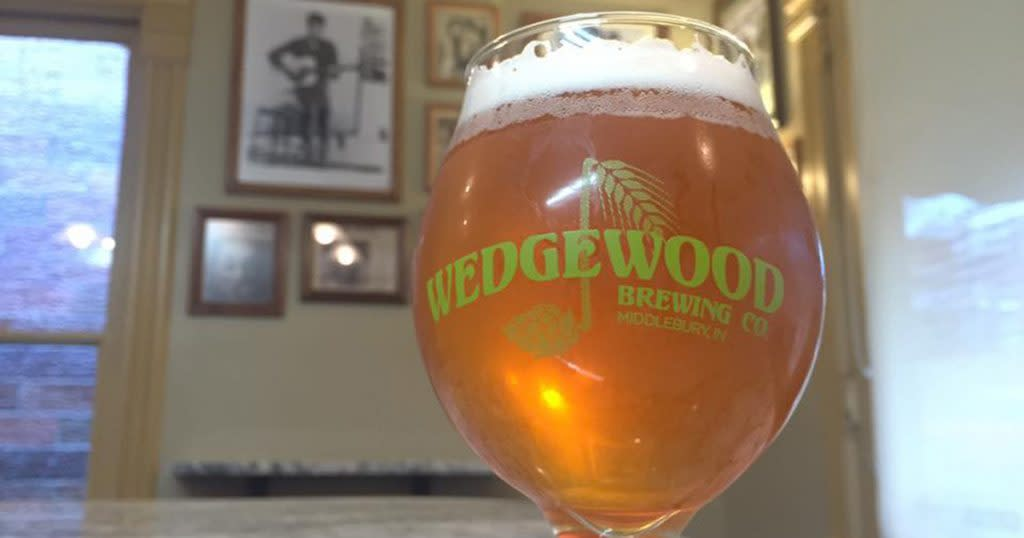 """Close up of a glass of beer with a thick head - the glass says """"Wedgwood"""" on the front"""
