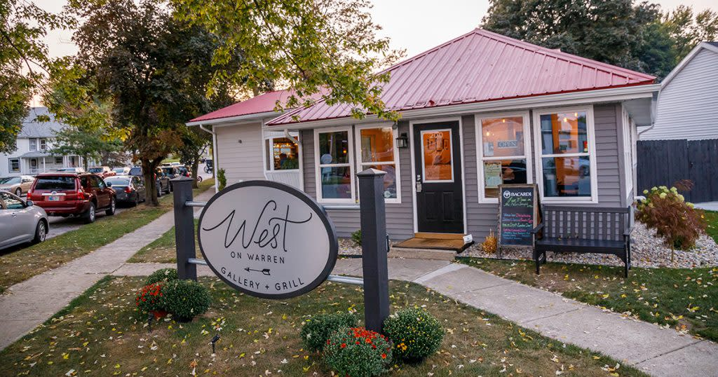 """A small building on a corner lot with a sign in front that says """"West on Warren Gallery and Grill"""""""