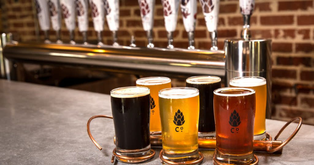 """A flight of six beers in glasses marked """"Co."""" sit on a bar in front of a row of white taps"""