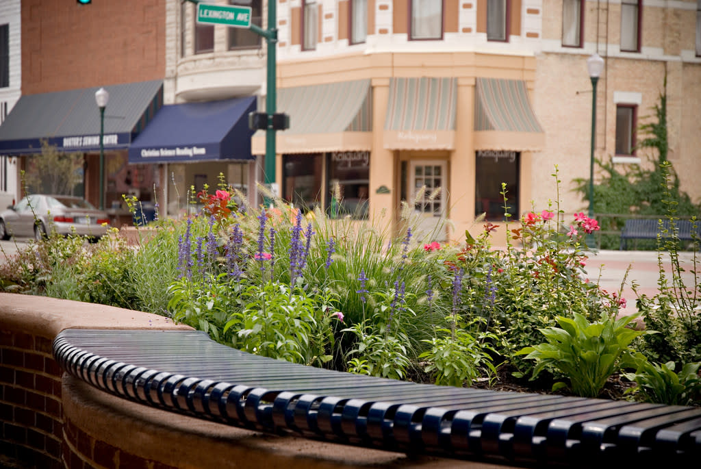 Close-up of a curved metal bench with a flower bed in downtown Elkhart, Indiana.