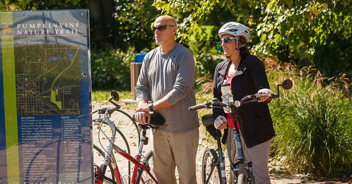 """A man and woman stand next to their bicycles as they look at a sign with a map that says """"Pumpkinvine Nature Trail"""""""