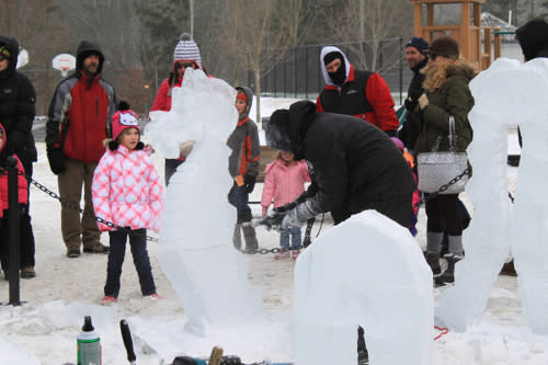 Winterfest attendees watching master ice carvers