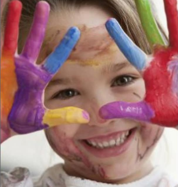 Toddler holds up painted hands