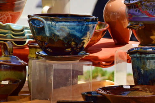 A table is spread with a variety of pottery