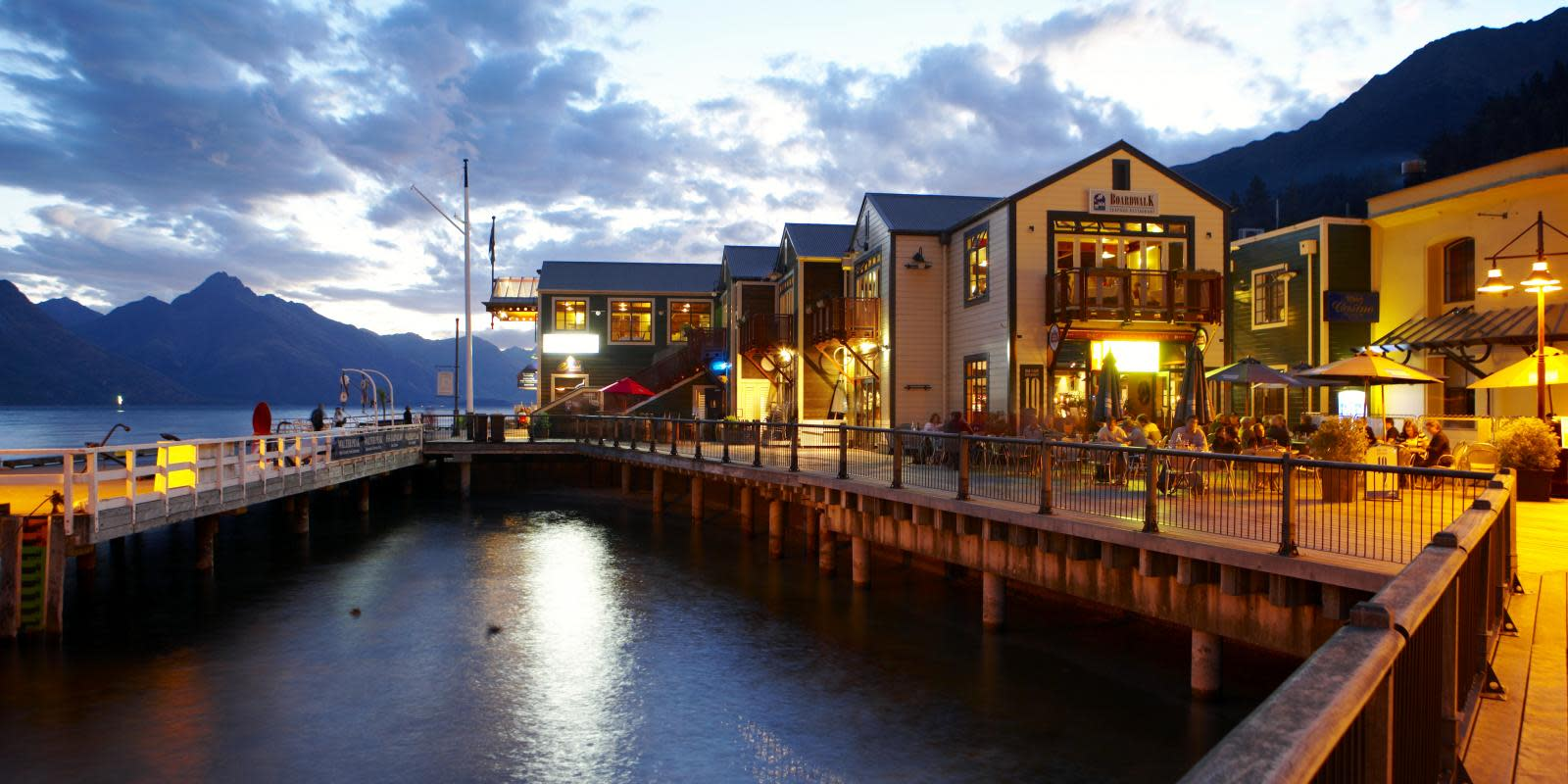 Steamer Wharf eateries at night, Queenstown Bay at dusk