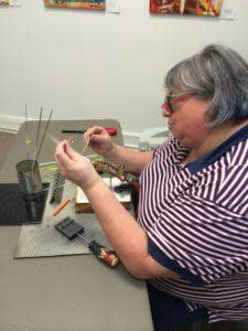 Glass artist, Linda, creating hand crafted beads at Le Originals