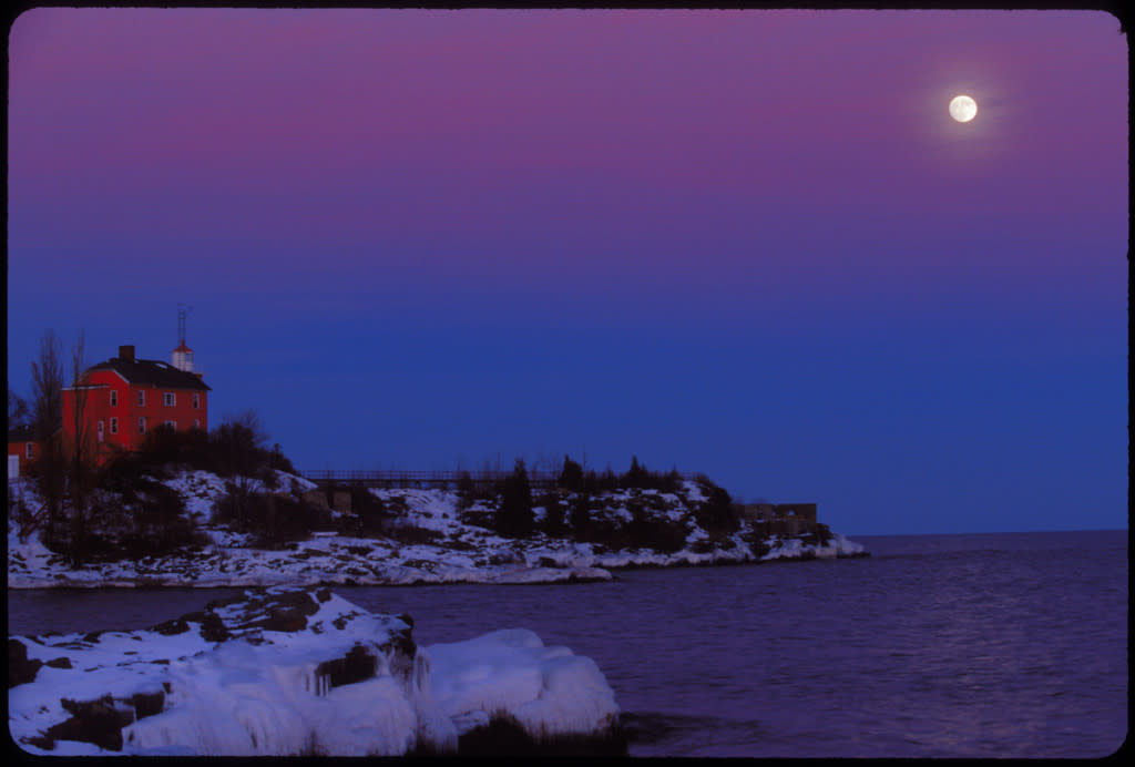 THE MARQUETTE LIGHTHOUSE WITH MOONRISE AND ICY SHORES IN WINTER IN MARQUETTE MICHIGAN.
