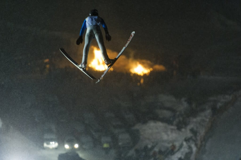 Ski jumping at night during a tournament at Suicide Bowl ski jumping area in Ishpeming, Michigan.