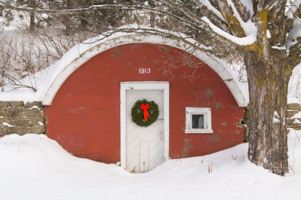 An old red root cellar with a Christmas wreath during a snowstorm.