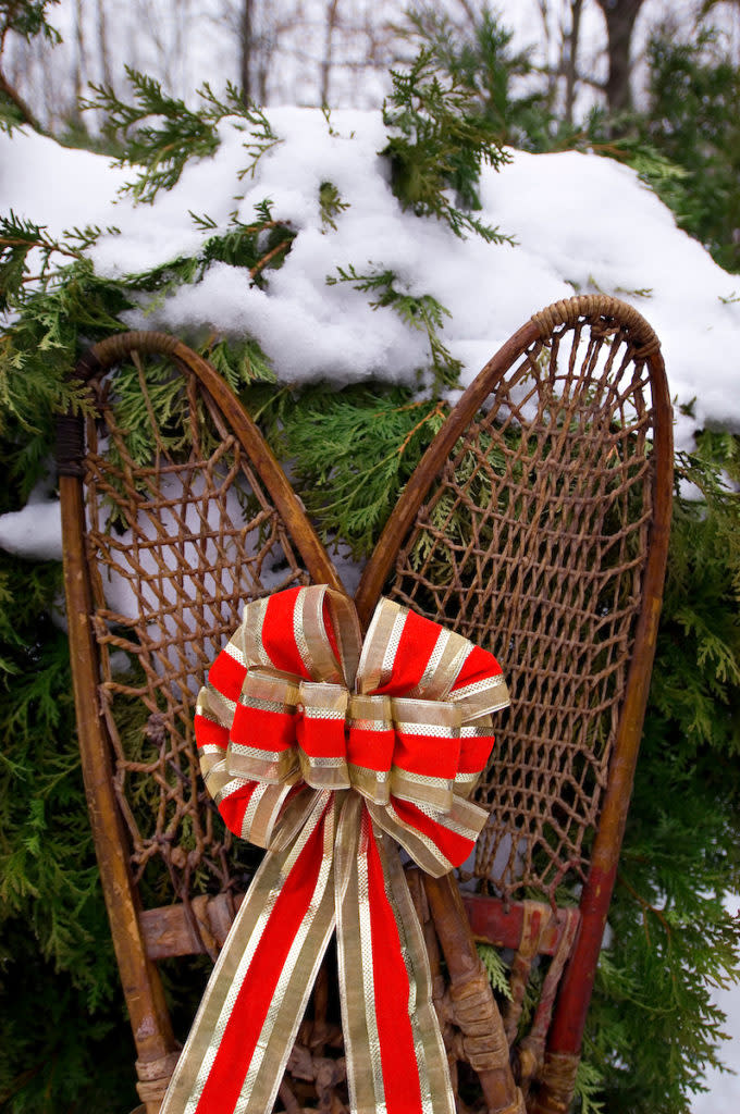 A pair of old wooden snowshoes are adorned with a ribbon as they rest against a cedar shrub in the snow in central Wisconsin during the Christmas holiday.