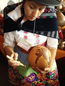 Bertha Aquino works intricate designs onto a gourd at the Santa Fe International Folk Art Market.
