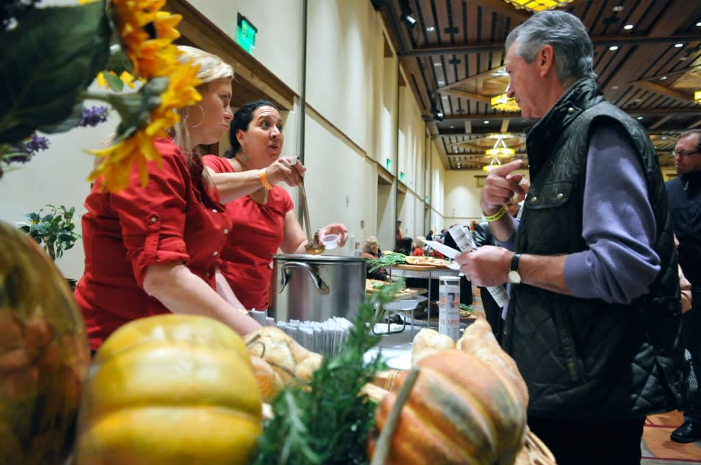 em012613c/jnorth/daily/From left, Shannon Papin and Karen Gascon, from Pizzeria de Lino, serve their cioppino soup to Paul Keshtkar during the 19th annual Souper Bowl. The fund raiser event for The Food Depot was held at the Santa Fe Community Convention Center, in Santa Fe, Saturday January 26, 2013. (Eddie Moore/Albuquerque Journal)