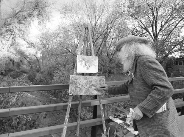 Tommy Macaione painting on a bridge over the Santa Fe River. (Photo courtesy of The Palace of the Governors Photo Archives, Negative HP.2014.14.1739)