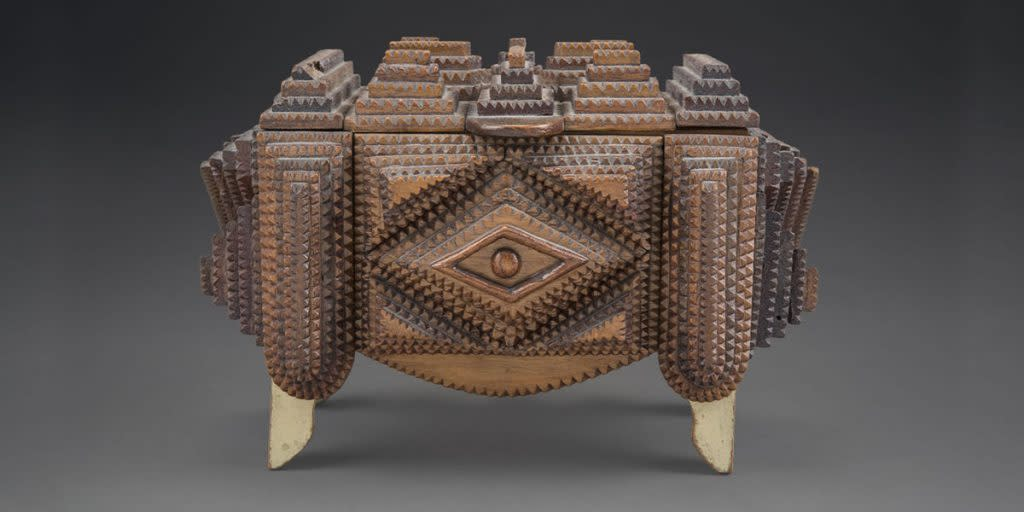 Tramp art definition, folk art of the 19th and 20th centuries utilizing recycled found materials, as cedar or mahogany cigar boxes, shaped into containers, lamps. Photo courtesy of MOIFA