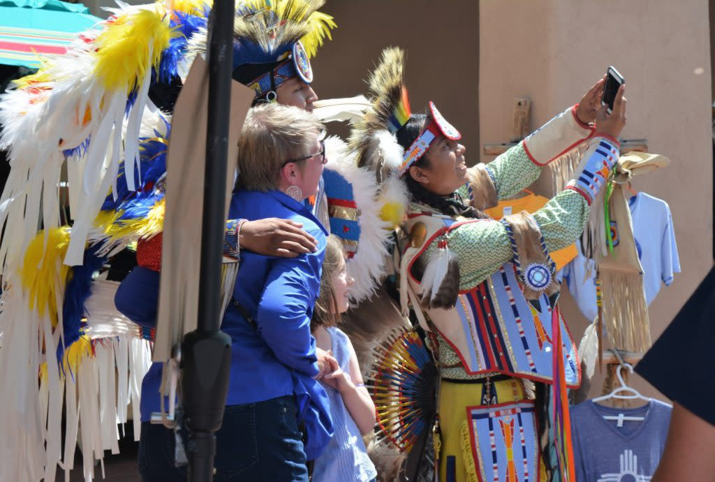 Santa Fe tourists enjoy taking a selfie with Native American Fancy Dancers during Indigenous Peoples Day