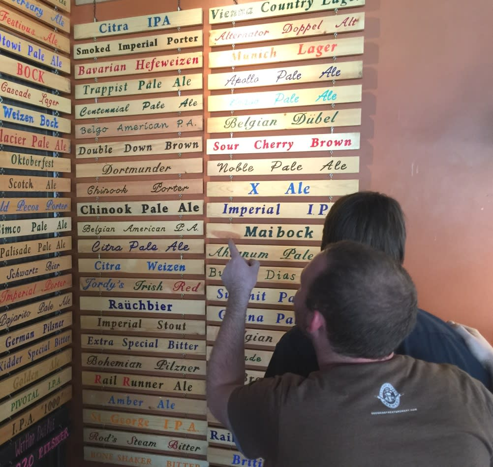 Second Street Brewery employees look over the extensive list of microbrews.