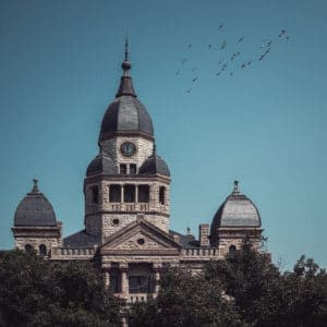 Denton's Courthouse-on-the-Square with a blue sky and a flock of bird flying above it