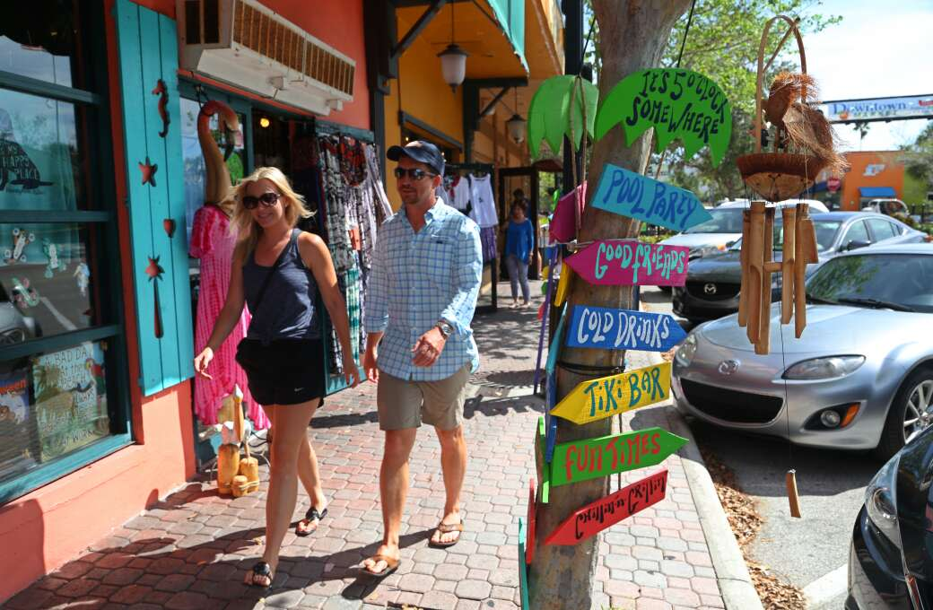 Visitors walk along Main Street in Dunedin, lined with shops and restaurants.