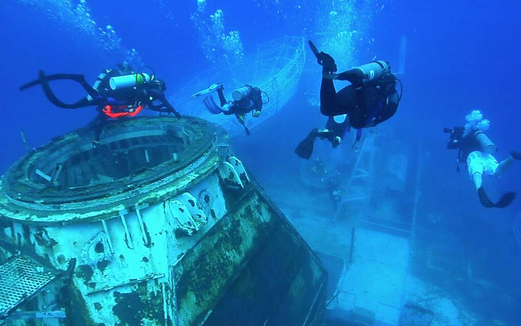 Divers swim around the United States Navy Ship General Hoyt S. Vandenberg