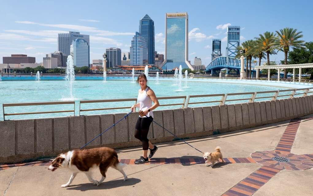 Katie Redding walks Jax, left, and Charlie, right, around Friendship Fountain in downtown Jacksonville.