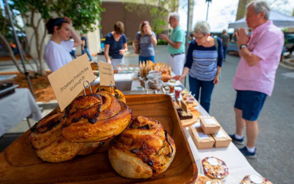 Customers browse and taste the offerings from 1748 Bakehouse at the Saturday morning Riverside Arts Market in Jacksonville.