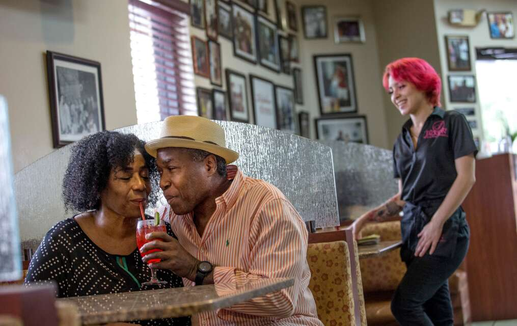 Newly engaged Vickie Jackson and Alfred McCullough share a fruit punch-lemonade at Jackson Soul Food while server Wendy Balbona tends to customers.