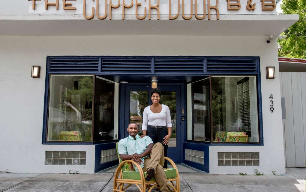 Akino West and Jamila Ross pose for a portrait outside their The Copper Door B&B in Overtown