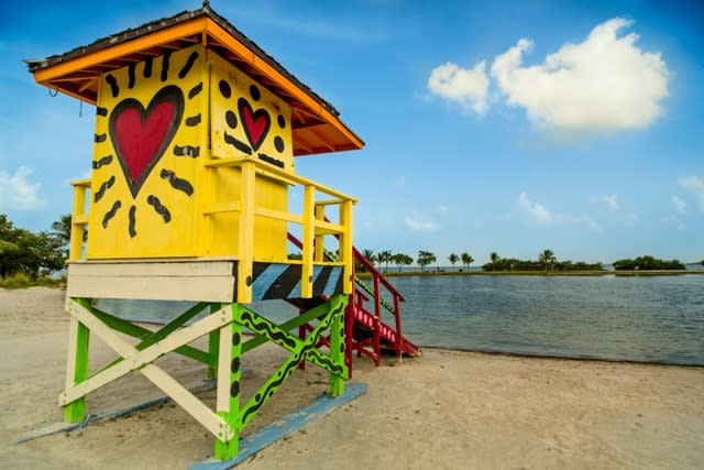 A yellow lifeguard tower with a heart by the beach in Miami