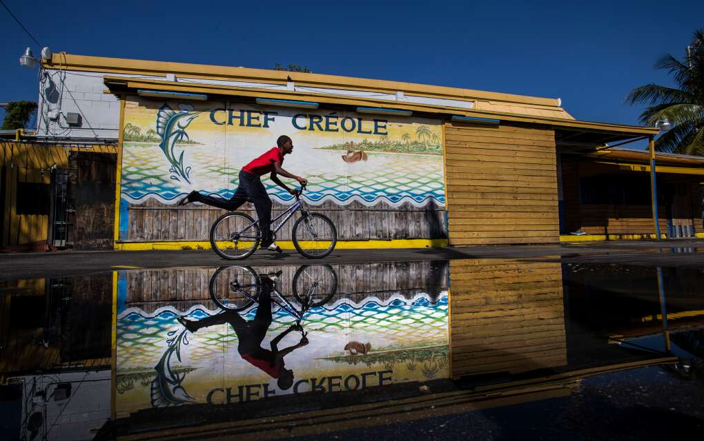 Jeremiah Martin, 14, rides his bike playfully past the Chef Creole restaurant at the corner of Northwest 2nd avenue and 54th street in Miami's Little Haiti neighborhood.