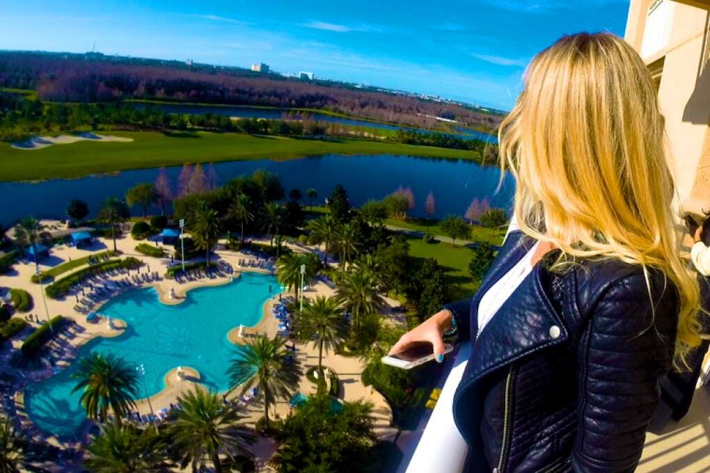 Woman viewing all of Orlando from the top of the Royal Suuite at the Ritz Carlton