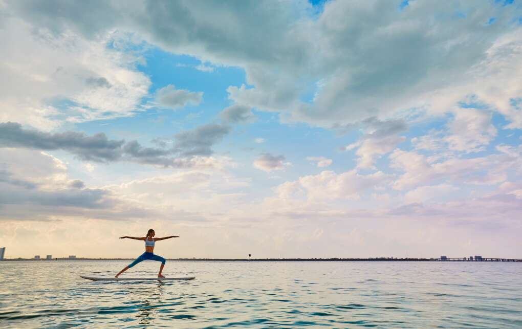 A woman practices yoga atop a paddleboard in Panama City Beach.