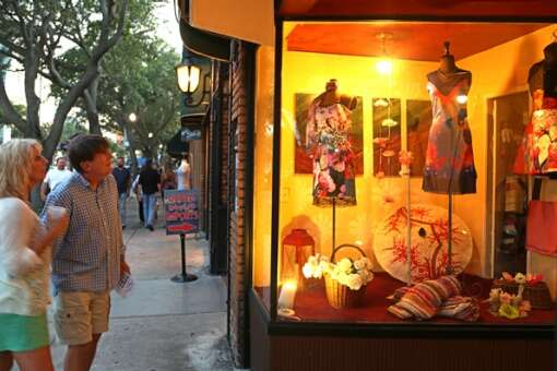 Shoppers admire Asian themed dresses in the front wind display of Cozette's Boutique in the 600 block of Central Avenue, St. Petersburg.