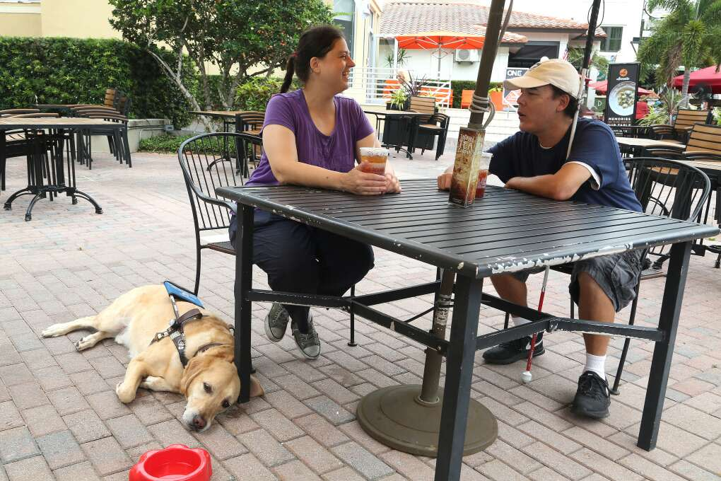 Katie Bandel rests and enjoys a tea along Beach Drive NE, St. Petersburg, at the Infused Tea Company with her guide dog Bo and her boyfriend William Marshall.