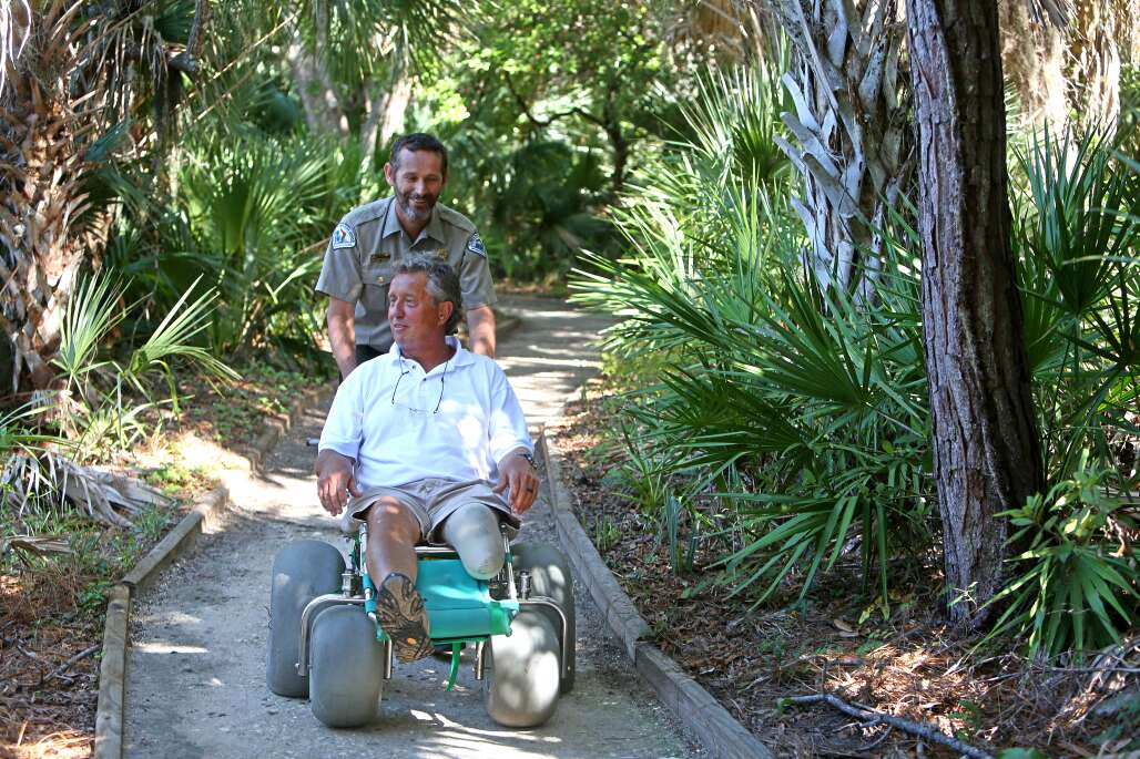 Rod Thomas of Osprey uses the Lester Finley Barrier Free Trail at Oscar Scherer State Park, with a wheelchair equipped with large tires. He gets assistance from Park Manager Tony Clements. The chair is available at the park.
