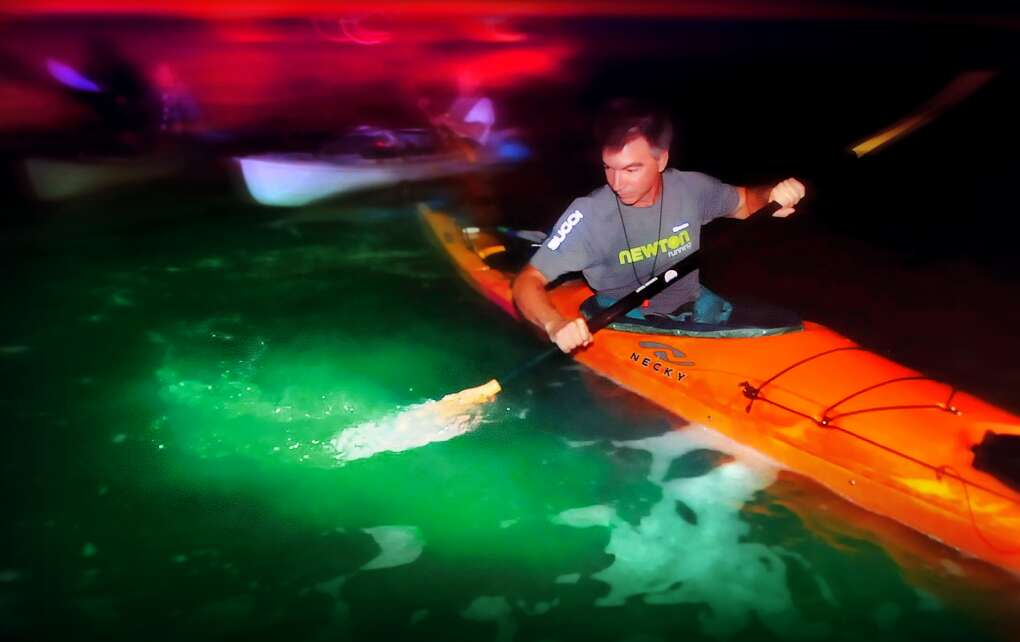 kayaker dipping paddle in water on Indian River Lagoon bioluminescence tour