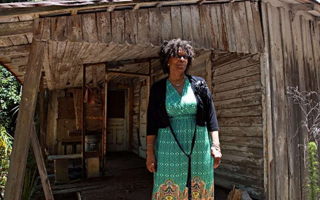 Martha Holloman Holley stands in front of the old Beal-Holloman midwife birthing home.