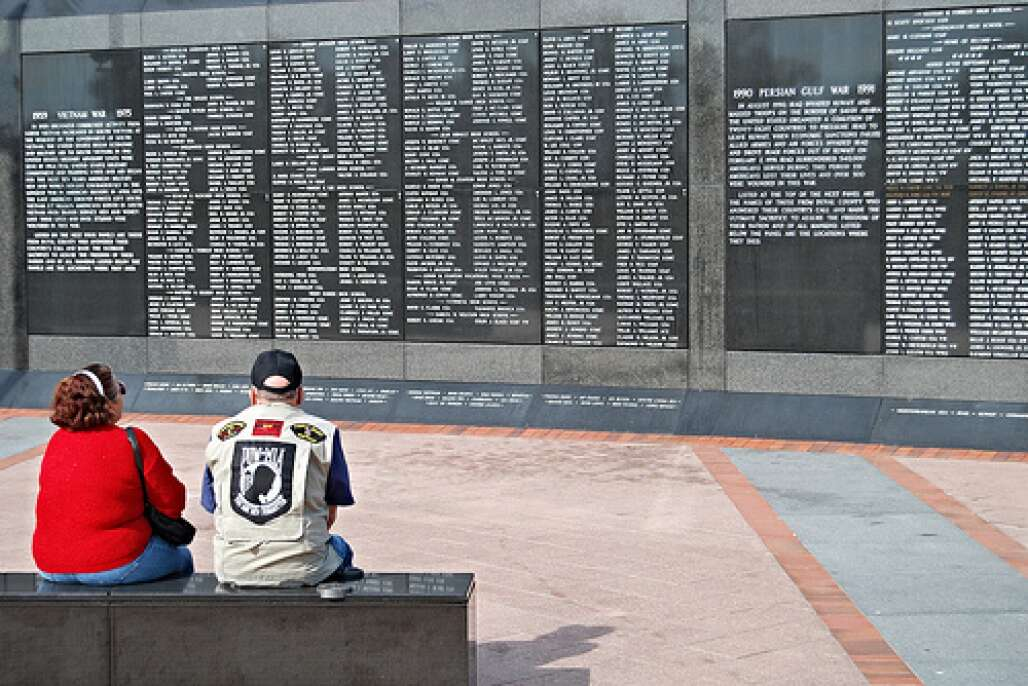 A couple sitting in front of the Veterans' Memorial Wall in Jacksonville
