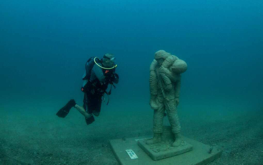A diver and statue face to face in Circle of Heroes