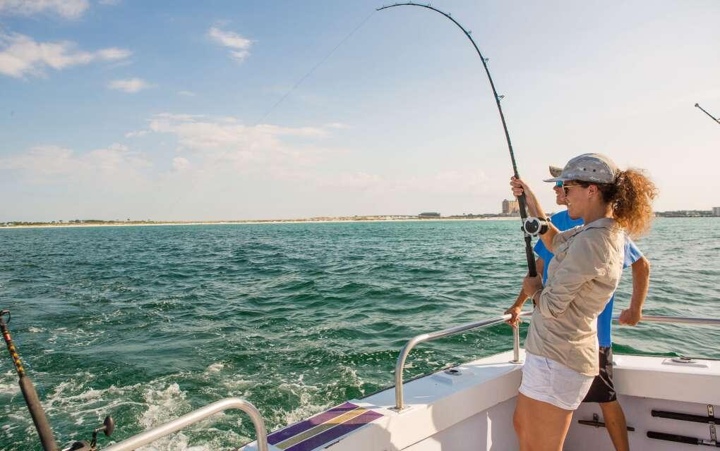 woman catching fish aboard boat in Destin