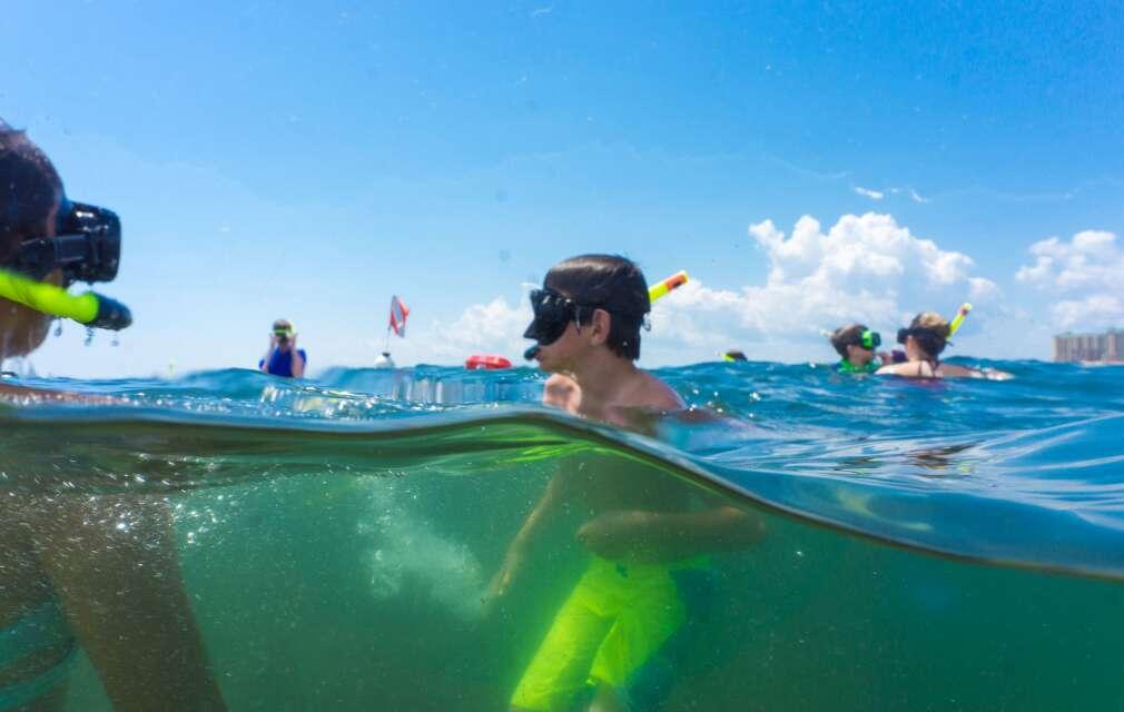 boy snorkeling in Destin, standing in clear water