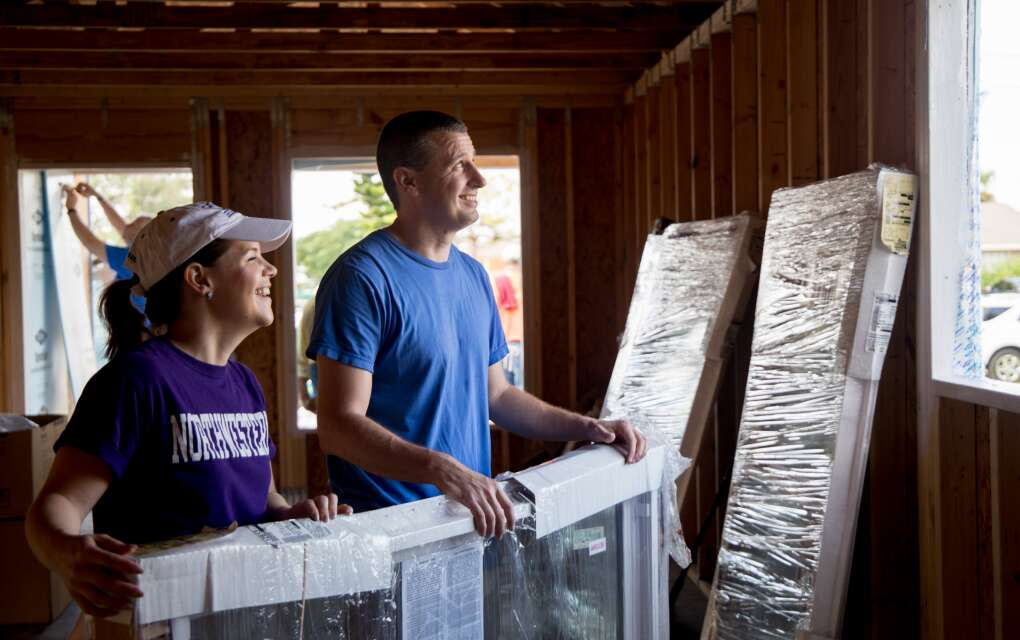 volunteers -- a man and a young woman-- help to build a house with Habitat for Humanity in Naples