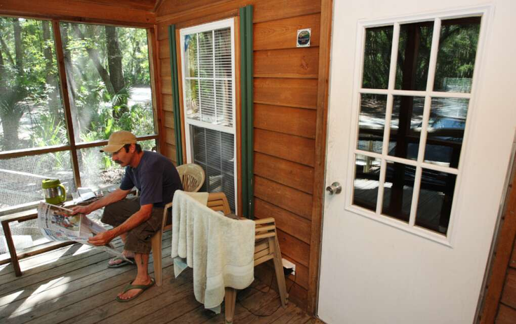 """Kathryn Abbey Hanna Park, Jacksonville,  front of """"cozy"""" cabin, man in rocking chair"""