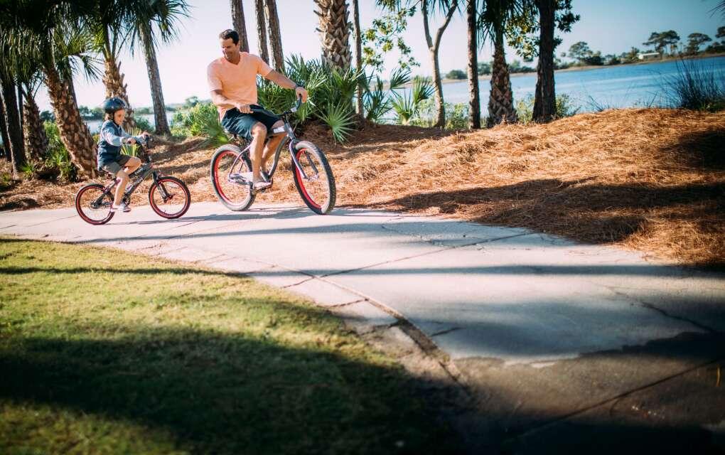man and child on bikes in Panama City Beach
