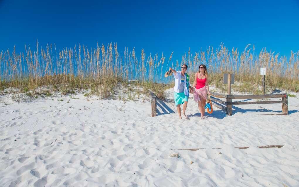 couple walking onto white sand Pensacola Beach