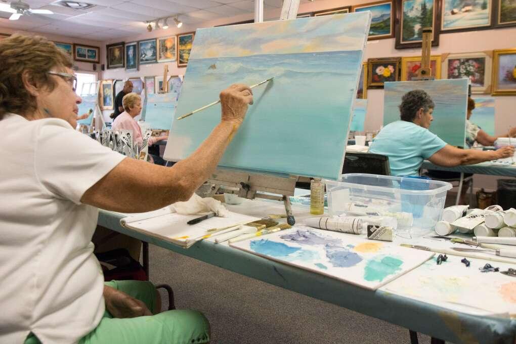 Rosemay Roseland works on her seascape at the Bob Ross Art Workshop.