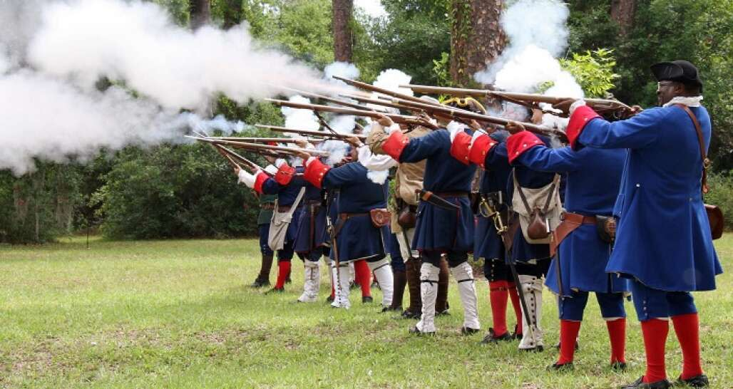 men in blue and red clothes shooting guns at Fort Mose Historic State Park