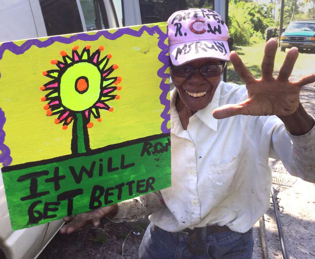 woman holding a sign saying It will get better