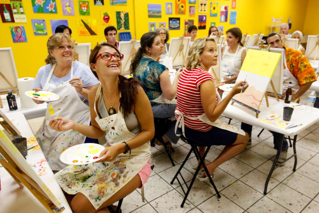 Savannah Newell, left, and Tonya Davis, right, watch as instructor David Durrett demonstrats how to paint a palm tree during the Artsy Palm painting class at Yes You Canvas.