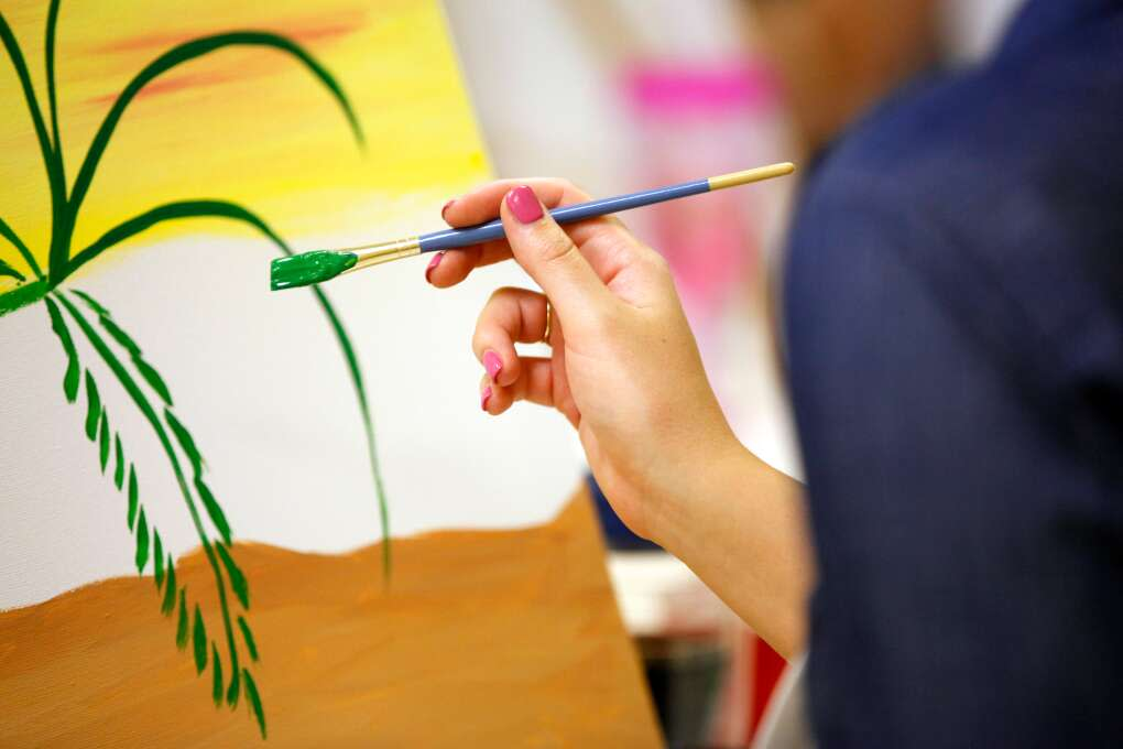 Tina Griffin paints a palm tree how to paint a palm tree during the Artsy Palm painting class at Yes You Canvas.