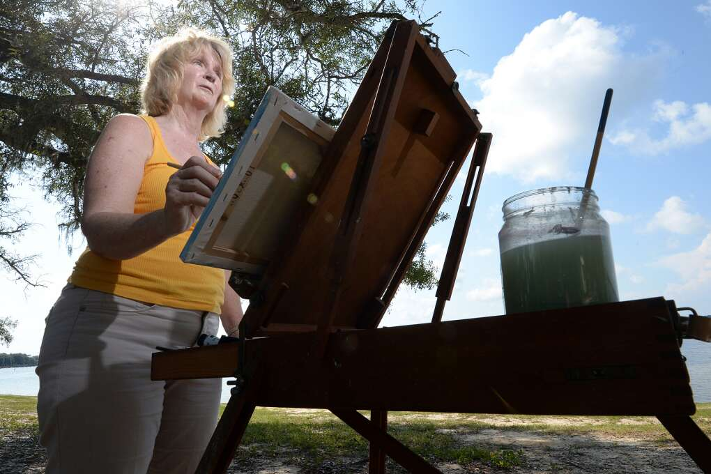 Helen Ballance, director of the Beach Art Group, paints air paints at Under the Oaks Park in Parker
